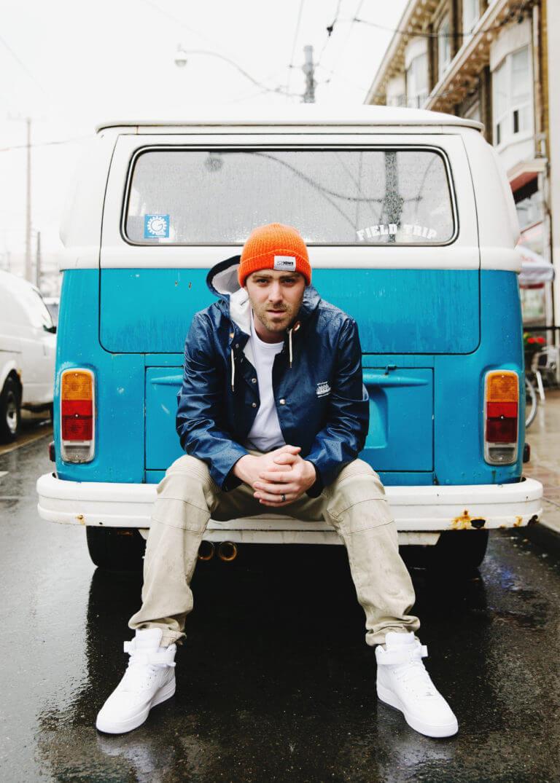 Classified singer sitting on back of VW van
