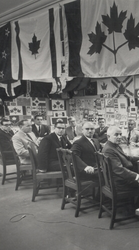 The all-party Parliamentary committee with the thousands of different designs submitted for the Canadian Flag, 1964, (detail). Original photograph by Cliff Buckman, digital enlargement from original photograph in the Collection of Queen's University Archives